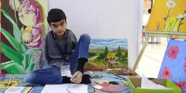 Doğuştan iki kolu olmayan Muhammet Uğur sol ayak parmakları ile resim yapıyor