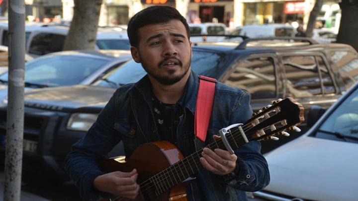 Kahramanmaraş'ta üniversite öğrencisi Alican Doğan sokak müziği yaparak harçlığını çıkarıyor